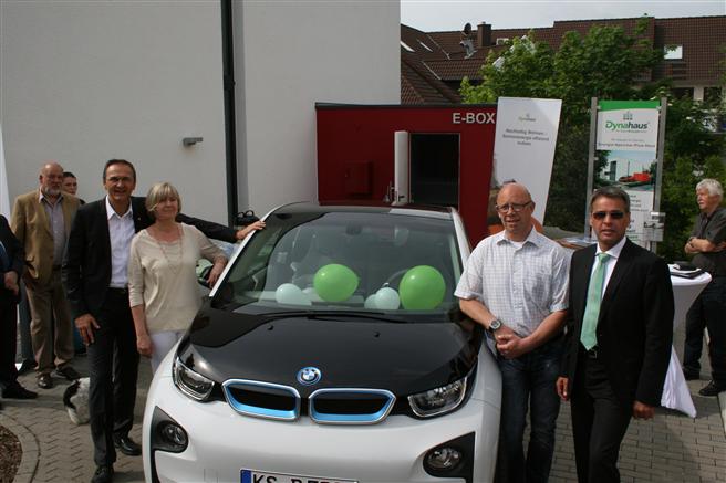 Testfamilie Freitag an ihrem neuen E-Auto, übergeben durch Matthias Krieger (Dynahaus) und Gotthold Heim (BMW) vor der E-Box inkl. E-Ladestation. © Dynahaus GmbH & Co. KG