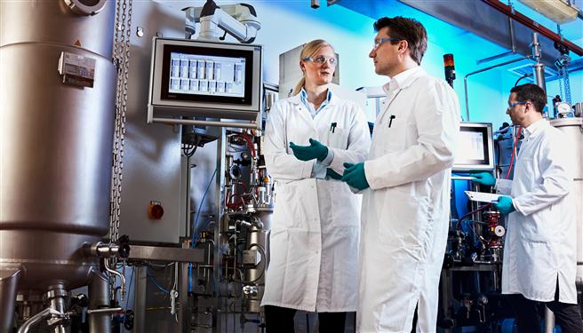 Herstellung von Bio-Anilin: Im kleinen Maßstab klappt der Prozess. Projektleiter Dr. Gernot Jäger (Mitte) arbeitet mit seinem Team (Dr. Swantje Behnken, links, und Dr. Wolf Kloeckner, rechts) daran, ihn auch in größeren Anlagen zu testen. © Covestro