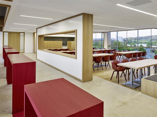 Das rote Möbelband zieht sich durch das gesamte Gebäude und findet sich auch in der sowohl für Besucher als auch Mitarbeiter offenen Cafeteria wieder. © Constantin Meyer, Köln