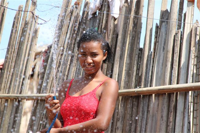 Da traditionell junge Frauen und Mädchen für die Bereitstellung von Wasser verantwortlich sind, sind sie von der Wasserknappheit besonders betroffen. Dieses Mädchen freut sich darauf, künftig die Schule besuchen zu können, anstatt Wasser zu organisieren. © Plan International