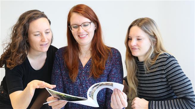 Ihr Handbuch 'Impulses for Innovative Teaching' ist für Hochschullehrer gedacht, die sich mit nachhaltigen Ernährungssystemen befassen. Die Masterstudentinnen (v. l.) Giulia Nentwig, Ina Kerkhoff und Lynn Marthe Garbers von der FH Münster haben es innerhalb eines EU-Projektes konzipiert und produziert. © FH Münster/Dzemila Muratovic